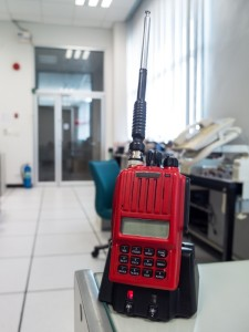 Red emergency two way radio on desk in factory.